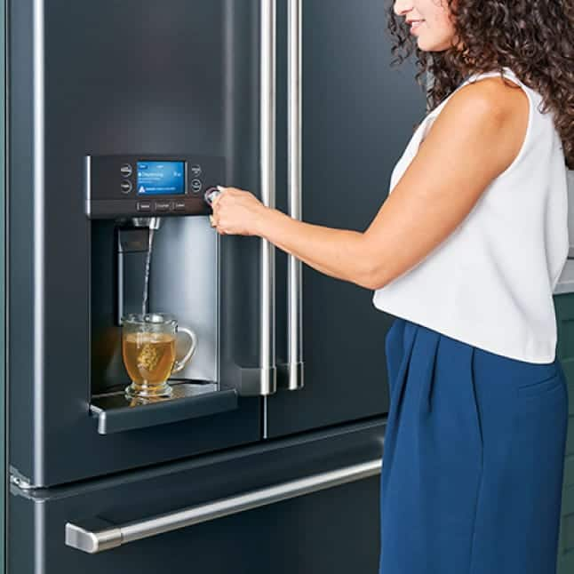 A woman dispenses hot water from her refrigerator