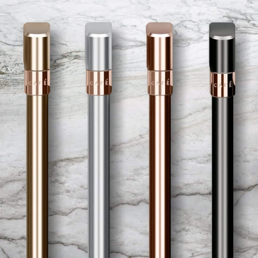 Brushed steel, brushed bronze, brushed black, and brushed stainless finish handles rest side-by-side on a marble counter.