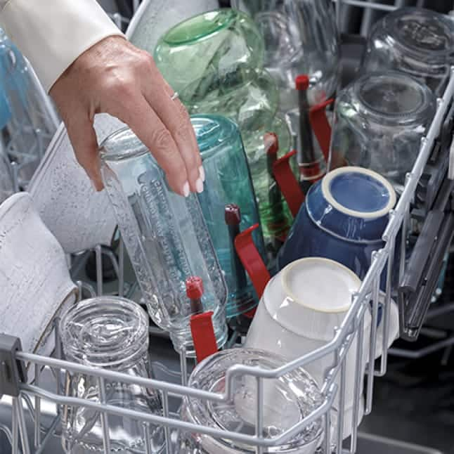 Someone loads glass and plastic bottles into their dishwasher.The bottle jets gently clamp the exterior and the nozzles go in the bottle's interior.