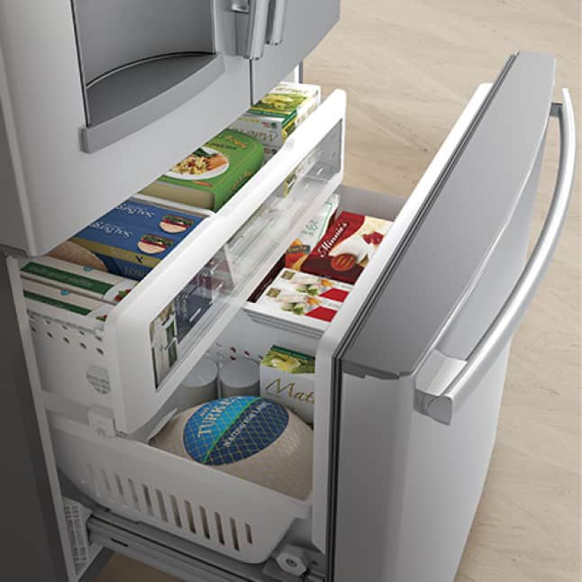 The freezer is opened, revealing a variety of frozen foods all neatly organized in baskets.