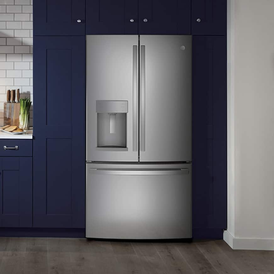 A conservative but stylish kitchen. GE Appliances with a stainless steel finish are installed in simple blue cabinetry.