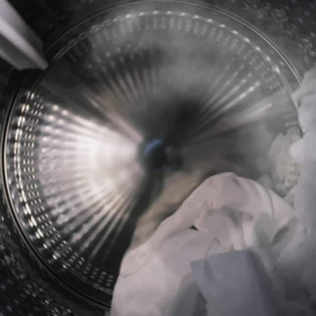 An interior shot of the drum shows several garments tumbling, surrounded by steam from the cycle.