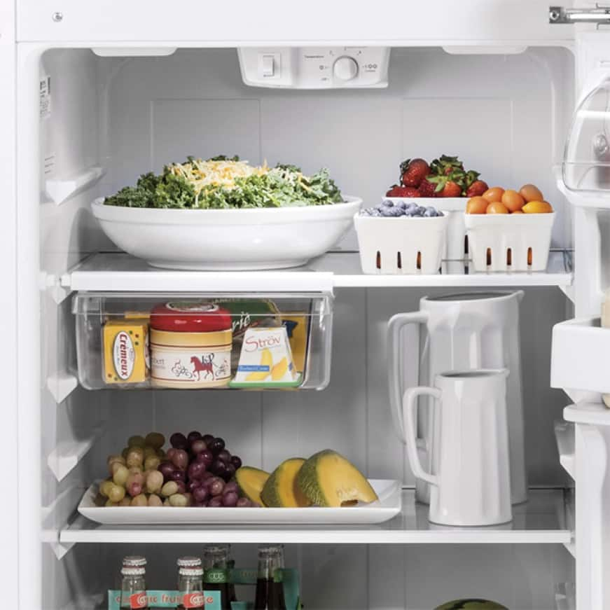 The open fridge is filled with a variety of foods on the glass shelving.