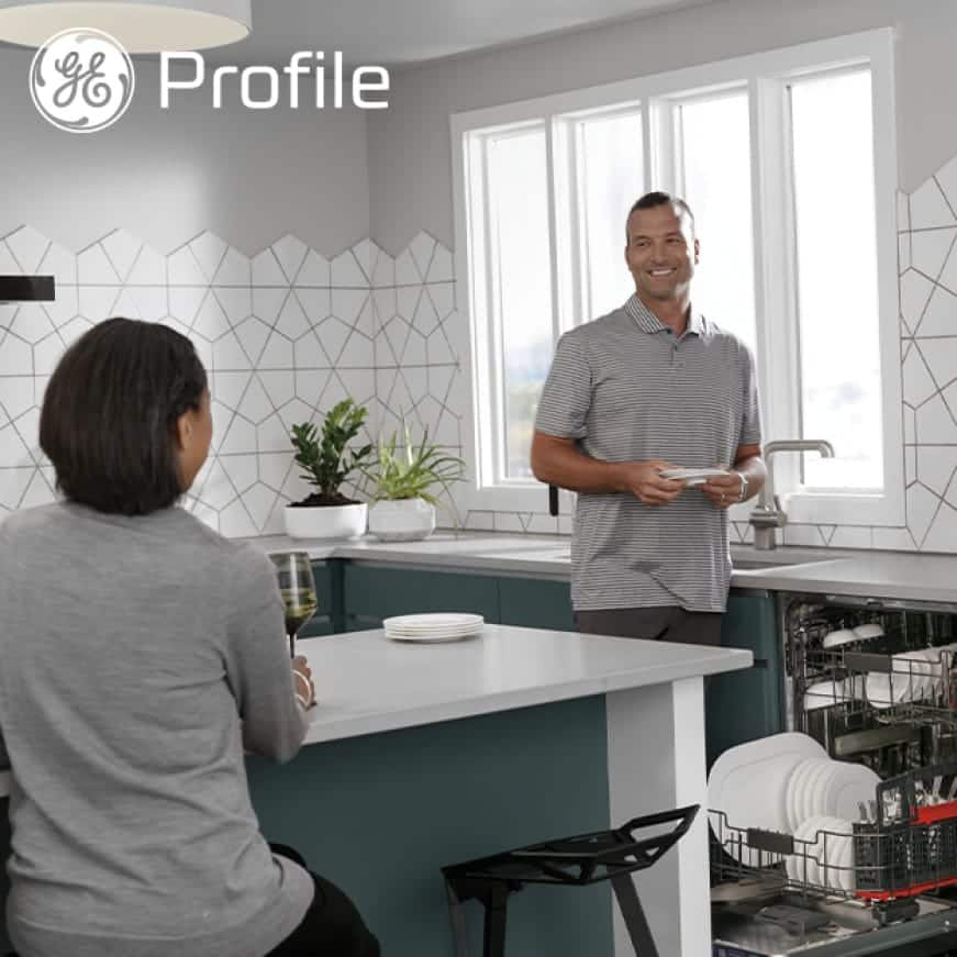 A couple put dishes away in their kitchen.The profile logo is superimposed in the corner