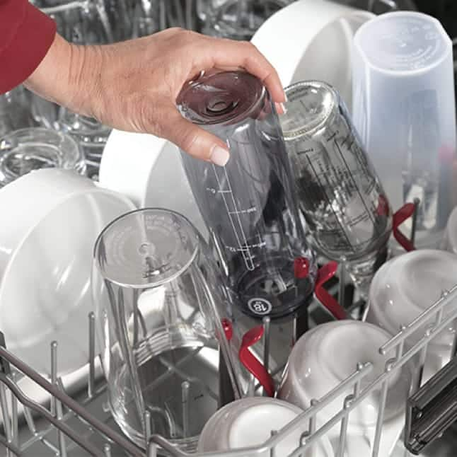 A hand places a bottle on the dedicated bottle wash jets