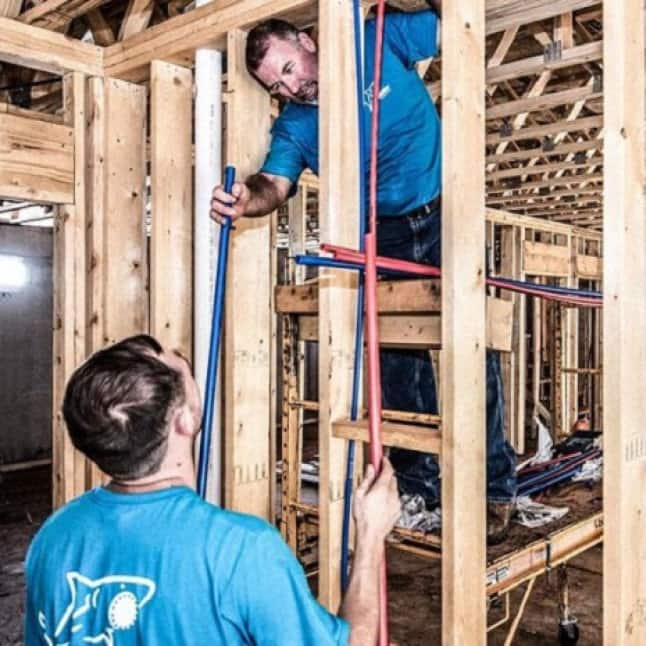 Men installing PEX Pipe behind a wall