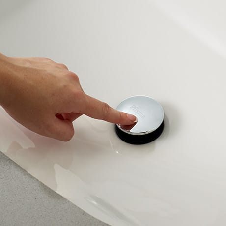 Hand pushes Push & Seal Drain to demonstrate opening and closing of drain