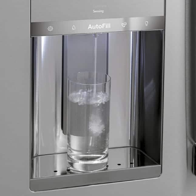 A glass pitcher sits underneath the fridge's water dispenser.A stream of water steadily fills the container.