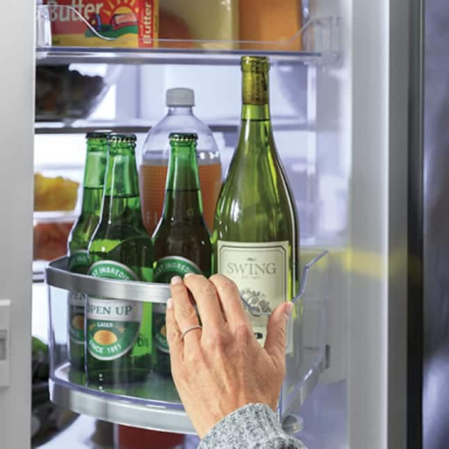 A hand swivels the rotating bin to access bottles in the extra door-in-door compartment