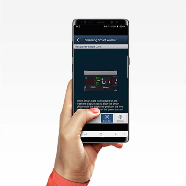 Person's hand holding smartphone as they access their washer settings remotely through Samsung Smart Washer/Dryer app.