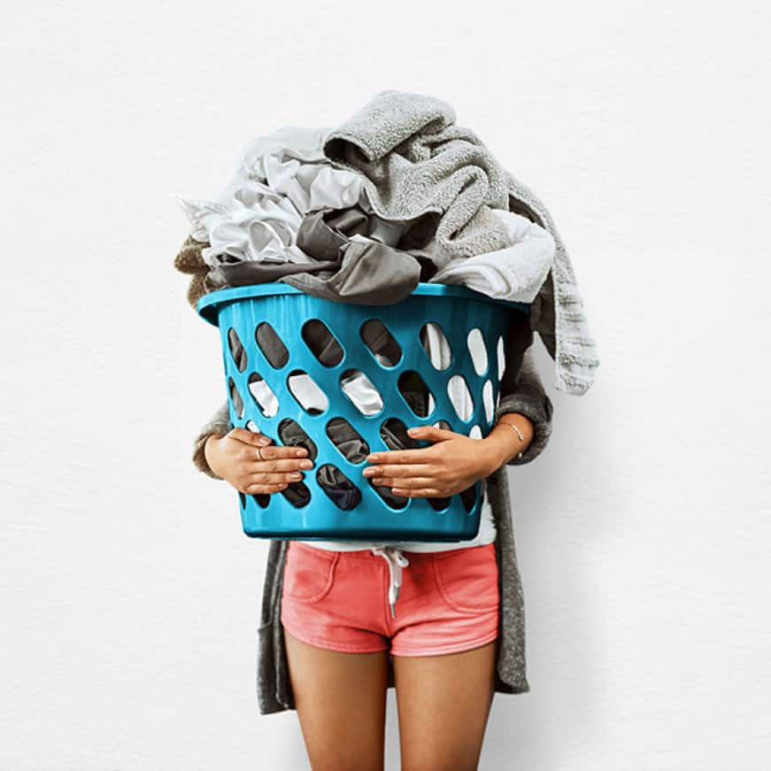Person holding large laundry basket full of clothes.