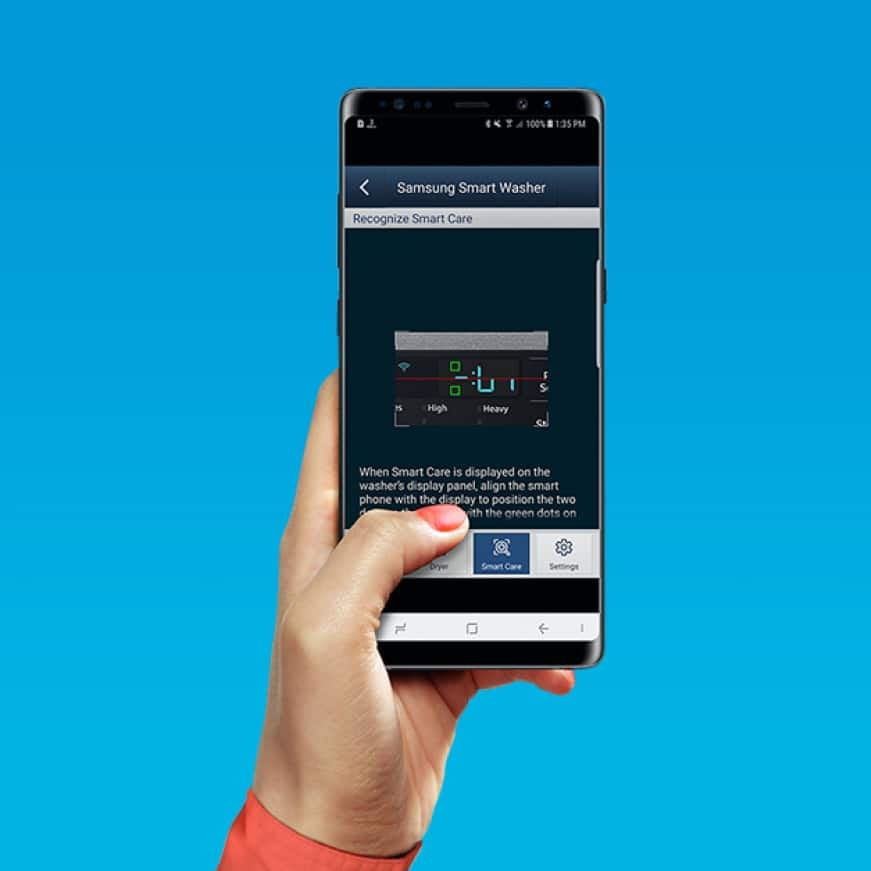 Person's hand holding smartphone as they access their dryer settings remotely through Samsung Smart Washer/Dryer app.