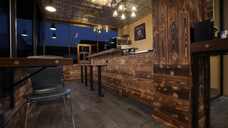 A coffee shop that has charred wood shiplap installed on their coffee bar and wall. This is gives it a more rustic look