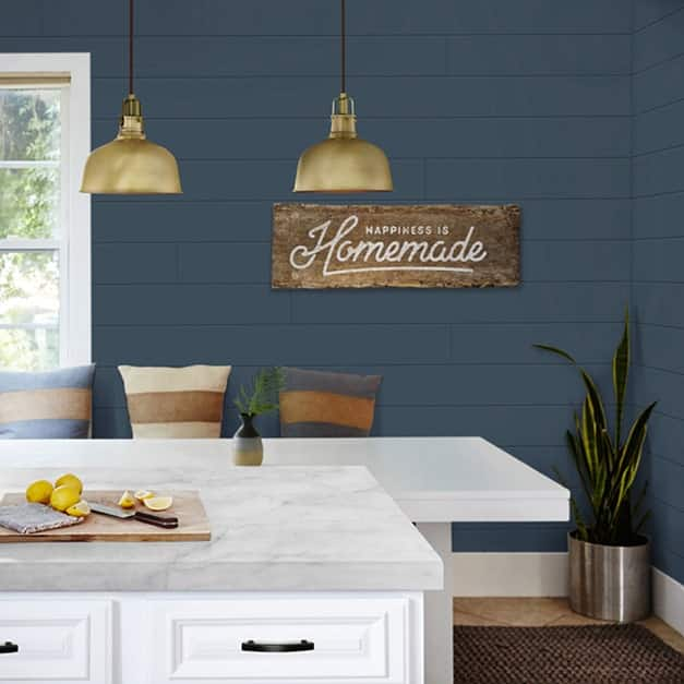 A country style kitchen with white cabinets and countertops showing the blue timeless shiplap installed vertically on the walls