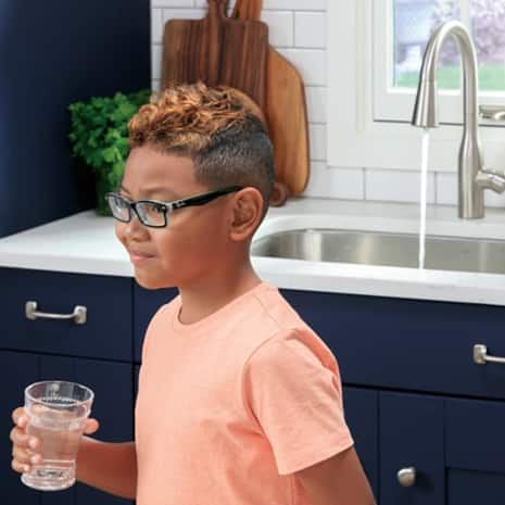 Young boy walking away from kitchen sink with faucet left running in background