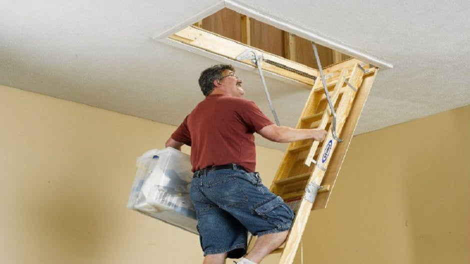 Man carrying box up the attic ladder