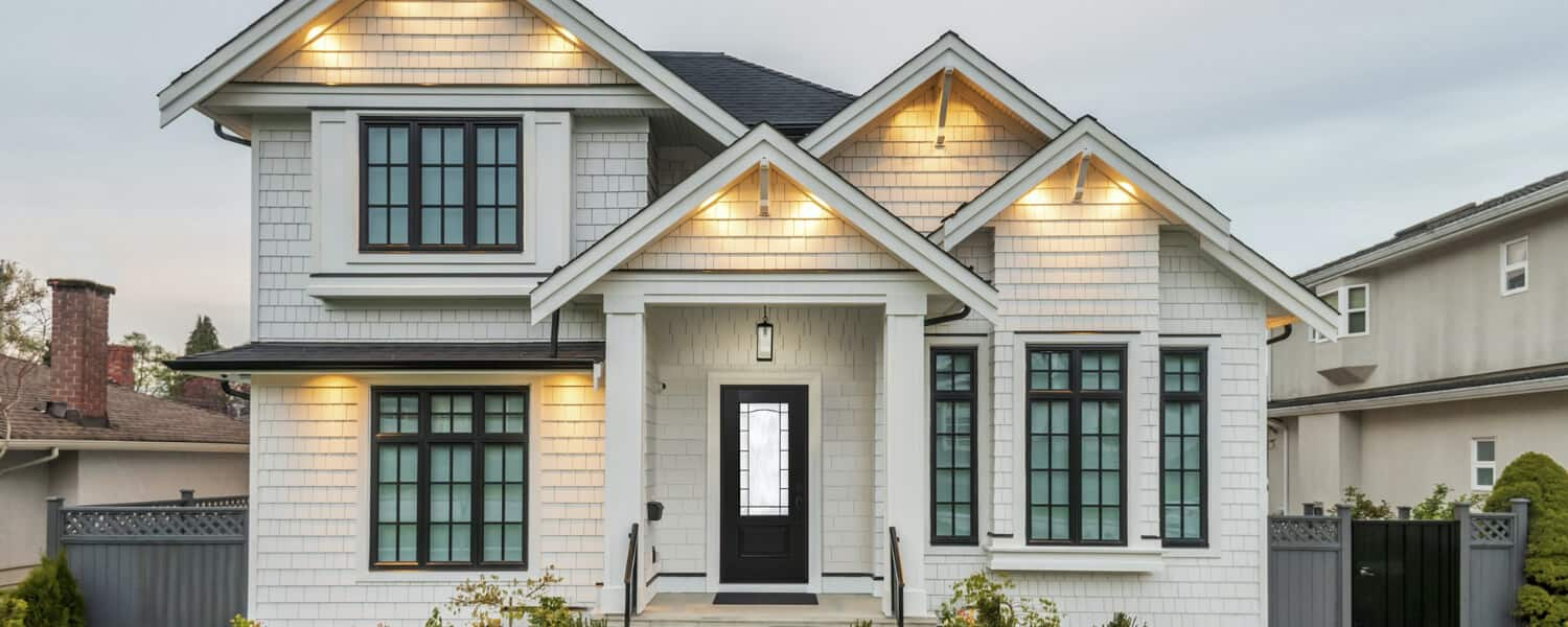 craftsman home trends - moss green house with stained oak door and half-stone pillars
