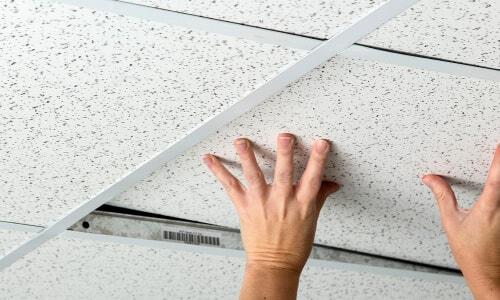 pair of hands lowering drop ceiling tile into grid