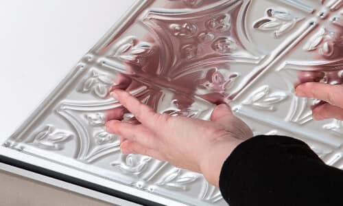 faux tin surface mount ceiling tile being installed