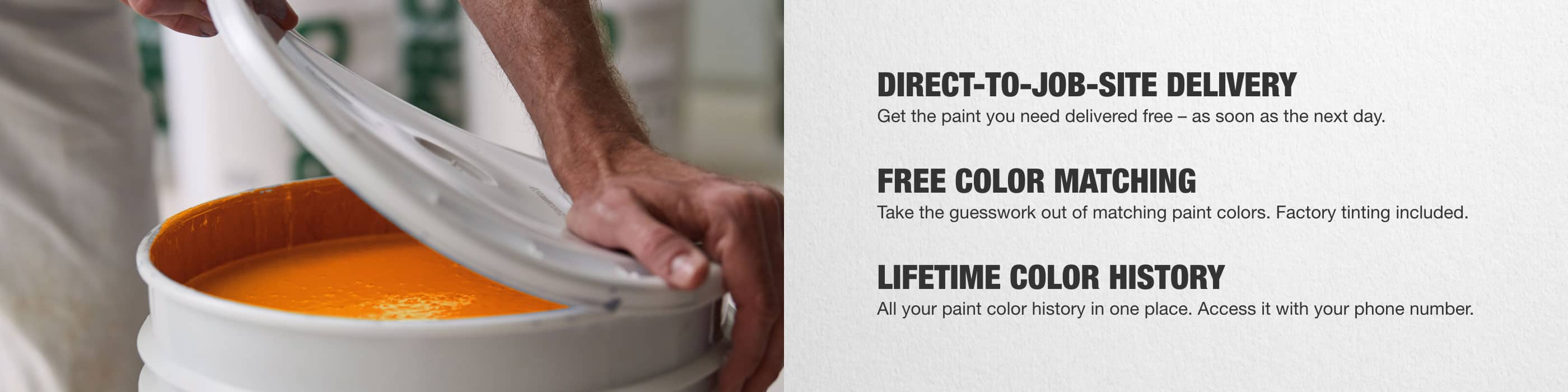 close-up of painter's hands lifting lid of a bucket of orange paint