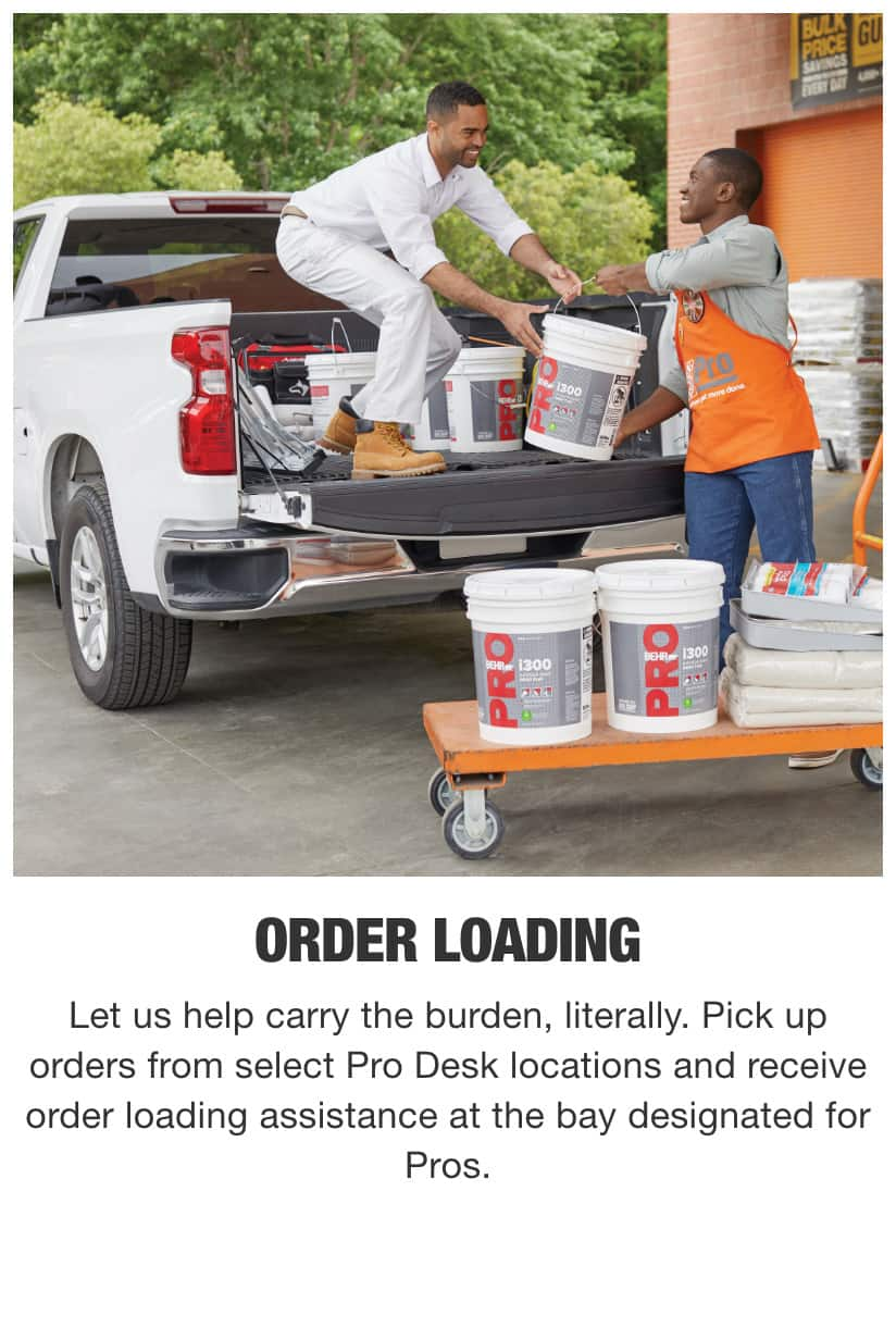 Associate Helping Painter Load Buckets Into Truck Bed