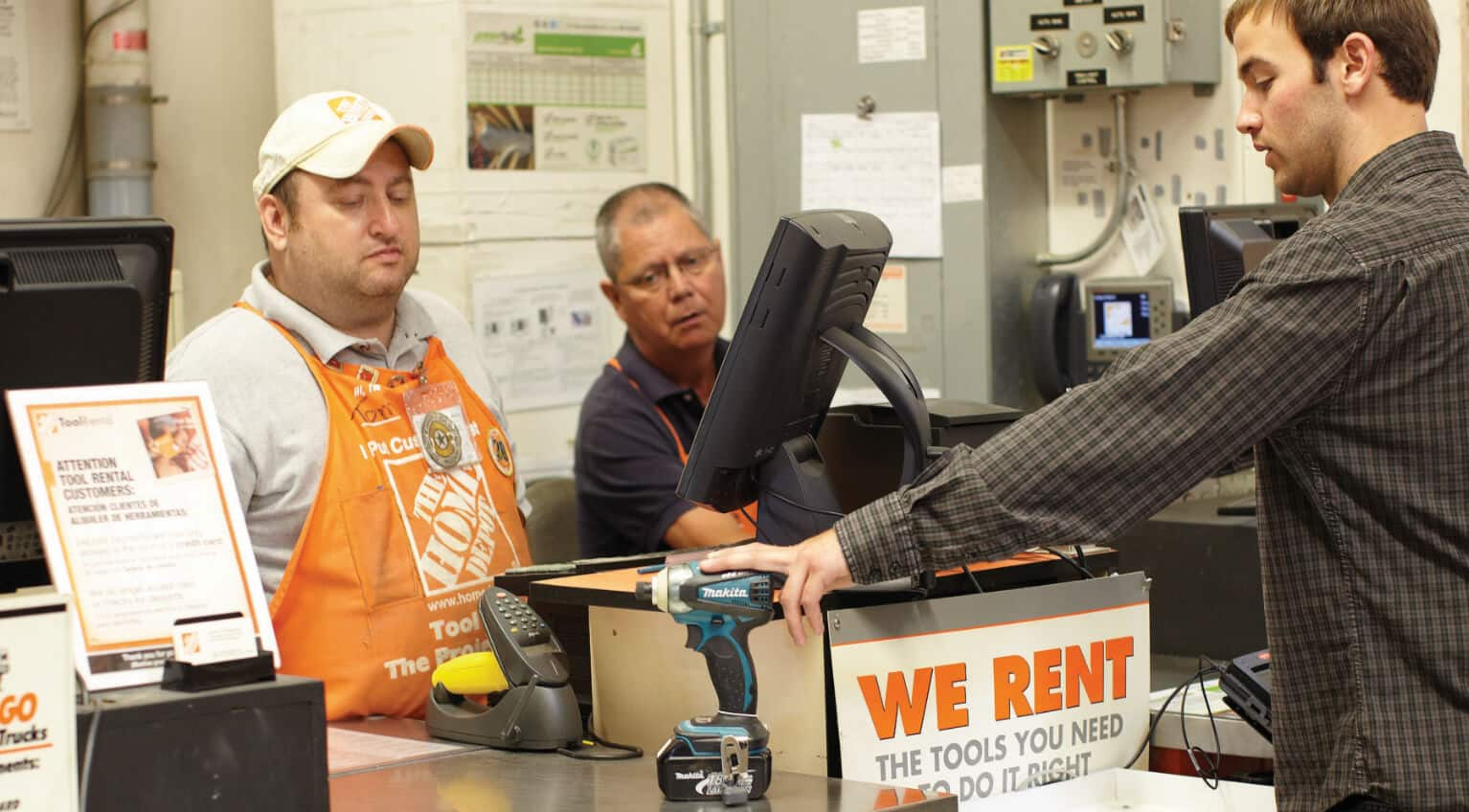 customer at The Home Depot rental desk renting an impact driver