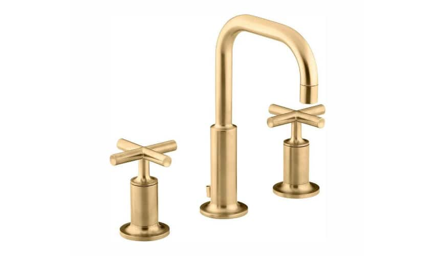 Photo of matte brass bathroom faucet with two knobs on either side of the spout