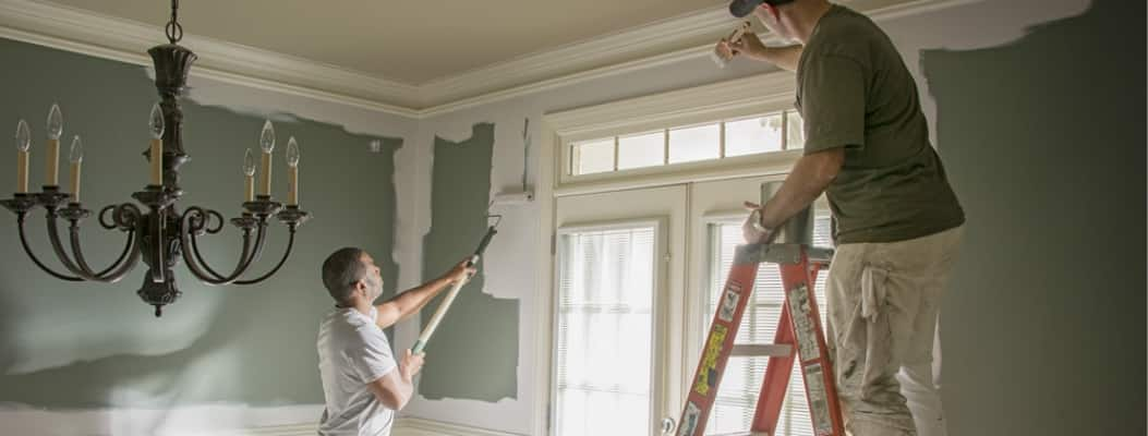 Two men painting inside home